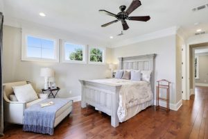 luxurious bed frame with wall mounted headboard in white white sofa with chaise & blue blanket dark toned wood board floors white walls accented by upper glass windows dark toned ceiling fan