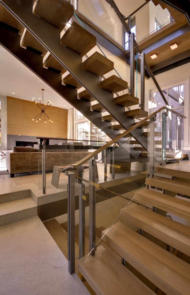 metal stair stringers wood treads beige floors glass railing sofa cabinet pendants ceiling lights contemporary design