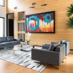 Modern Couches In Grey Glass Top Coffee Table In Rectangular Shape White Grey Area Rug Colorful Abstract Painting Wood Colored Floors & Walls