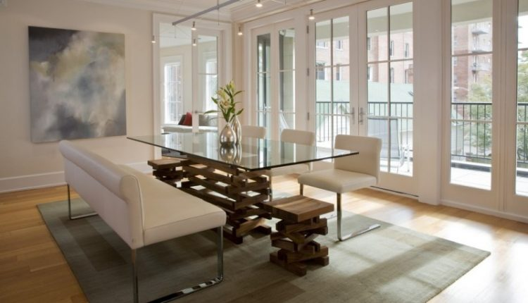 modern glass kitchen table with white chairs and benches with metal legs cream rug light toned wooden floor glass doors anging lamps wall artwork