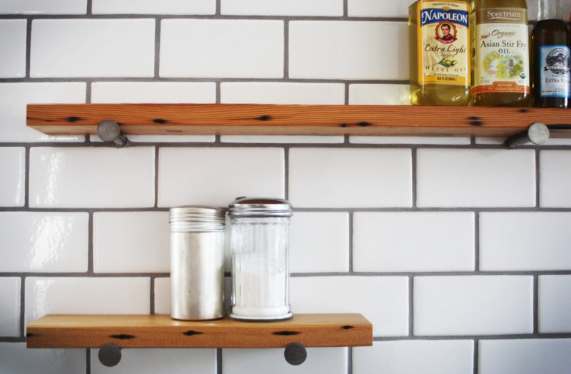 modern industrial kitchen shelves made of hardwood and supported by black wrought iron stands