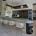 Modern Kitchen And Bar Modern Bar Stools In Soft Color Natural Stone Counter Glass Top Bar Table With Side Wine Rack Pale Toned Wood Floors Recessed Stainless Steel Appliances In Dark Finishing