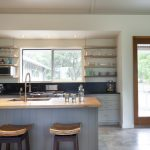 Modern Kitchen With Industrial Open Shelves Centered Glass Windows Light Grey Kitchen Cabinets Wood Top Kitchen Island With Light Grey Base Two Bar Stools Black Backsplash