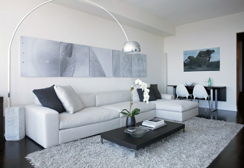 modern living room white sectional with white & black accent pillows low level coffee table in black white wool area rug black laminated floors white walls with abstract paintings