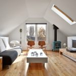 Modern Living Room With Slanted Ceiling Skylight Glass Windows Medium Toned Wood Floors Modern Couch Modern White Coffee Table Wood Media Console A Pair Of Wood Chairs
