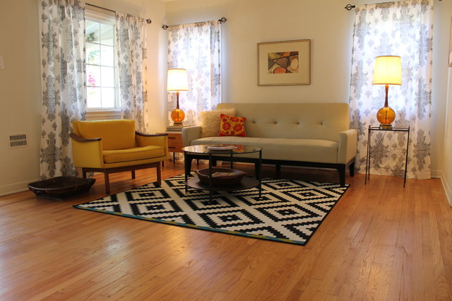 modern mid century living room furniture set consisting of bright yellow chair neutral colored couch and pillows white black tribal rug medium toned wood floors glass top center table