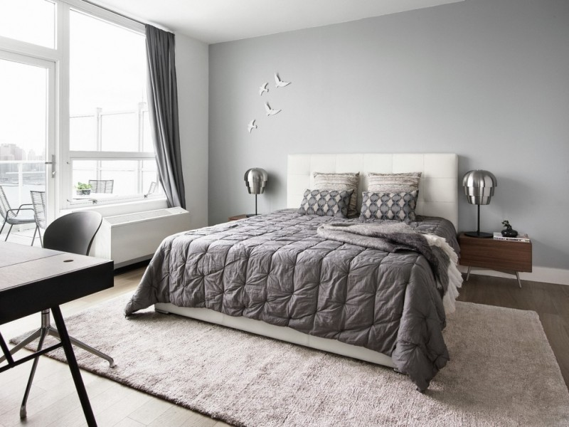 modern minimalist bed frame with white headboard silver toned bedding idea light grey rug minimalist bedside tables with metal table lamps large glass windows with grey draperies light blue walls