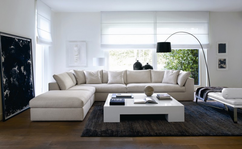 modern minimalist living room white minimalist sectional in L shape clean & compact coffee table blackwashed area rug dark hardwood floors white walls