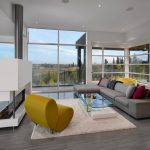 Modern Minimalist Style Living Room Grey Sectional With Colorful Accent Pillows And Chaise Yellow Chair White Area Rug Two Sided Modern Fireplace With White Concrete Surround Grey Floors