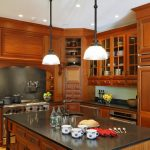 Modern Rustic Kitchen Idea With Wooden Kitchen Cabinets Wooden Corner Cabinet Stainless Steel Appliances Black Top Kitchen Island With Storage A Couple Of Classic Pendant Lamps