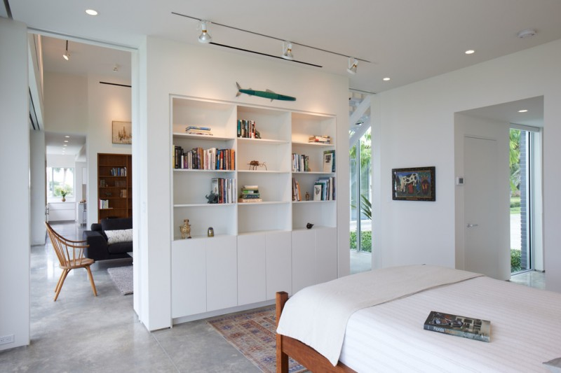 modern style bedroom with wood bed frame white wall partition with recessed bookshelves concrete floors