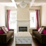 Modern Style Living Room Dark Couches With Magenta Accent Pillows White Upholstery Table Standard Fireplace Colorful Stripes Draperies White Walls Crystal Chandelier