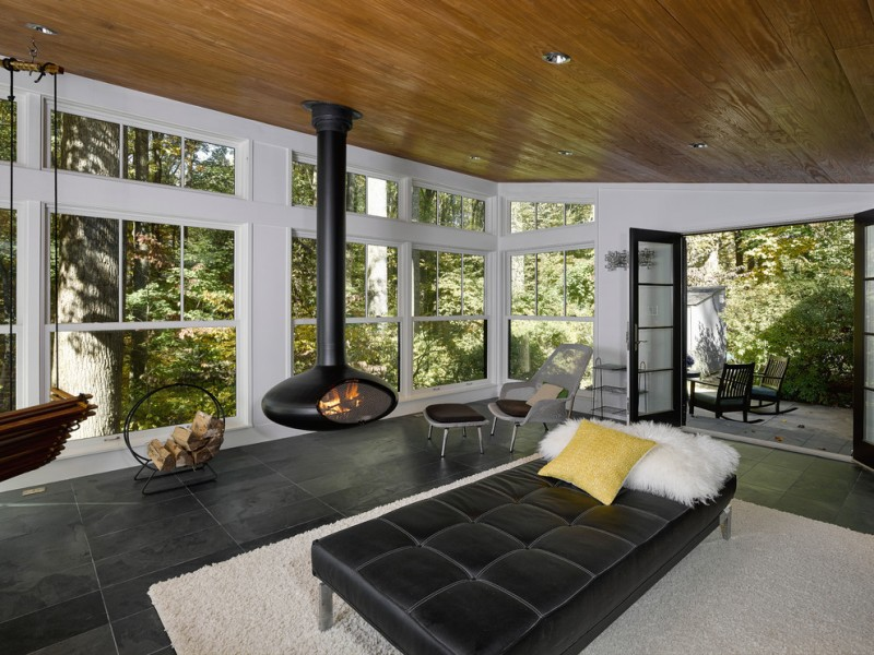 modern style sunroom black hanging fireplace black leather daybed furniture with accent pillows fluffy white area rug black slate floors standard wood ceilings