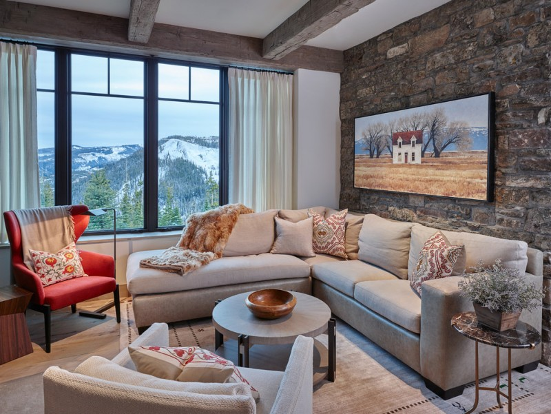 mountain style living room idea neutral toned sectional red corner chair neutral toned rug neutral toned table in round shape hard textured stone walls white ceilings with exposed logs