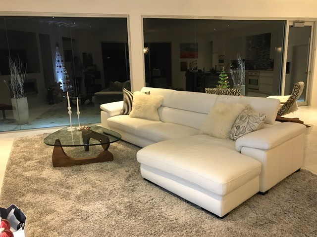 open concept living room in contemporary style white couch with accent pillows clear glass top center table with dark wood base light grey area rug porcelain floors
