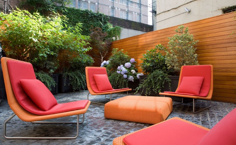 outdoor chairs in orange with red cushion and pillows, and orange square ottoman as coffee table