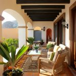 Porch Roof Designs Black Beams Rustic Porch Furniture Potted Plants Terra Cotta Tiles Porch Arches Wall Lanterns Grean And Cream Pillows