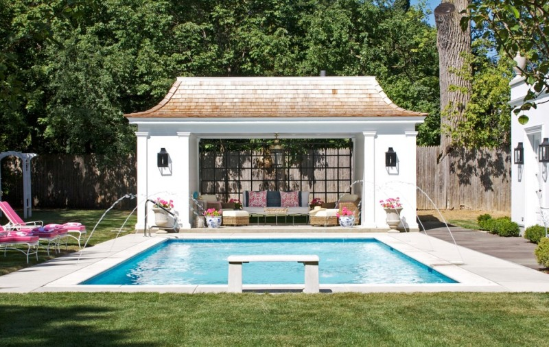 rectangular pool house with ombre brown roof, white walls, open living room with rattan sofat set with white cushion, windows on the back, classic pendant lamp, blacks sconces