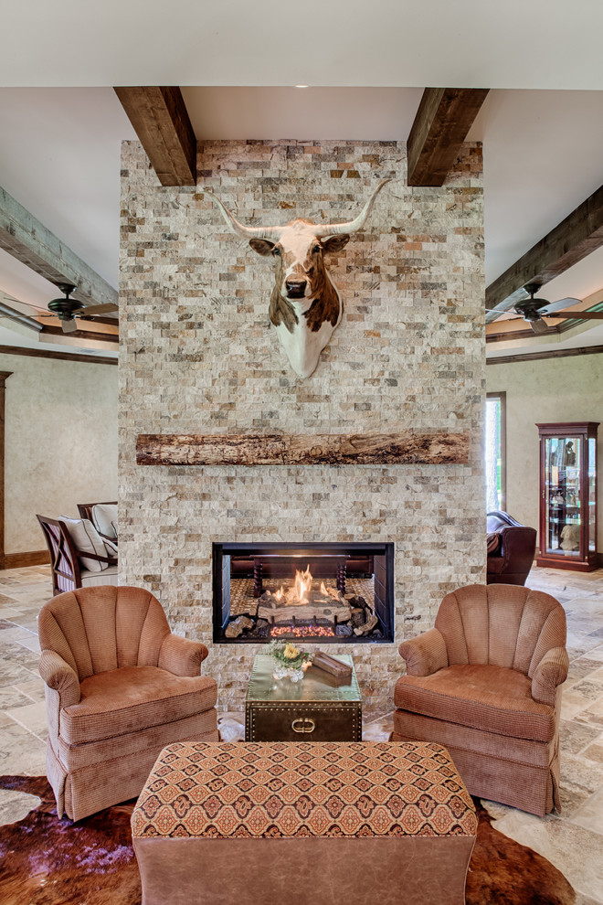 rustic living room idea lighter brick walls with decorative deer's head two sided standard fireplace a couple of couches in light brown light brown ottoman table glass top side table