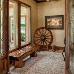 Rustic Style Entry Hall Idea Glossy Top Wood Entry Bench Decorative Wheel In Rustic Look Area Rug With Motifs Rustic Pendant Lamp Beige Painted Walls Beige Ceilings
