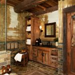 rustic vanities in wood planks with black handles, black marble countertop, brown tiles one line backsplash, square wooden framed mirror, sconces