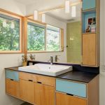 simple bathroom vanity with blue color blocks on the top drawer, black countertop, white sink, metal faucet