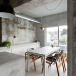 Small Industrial Kitchen In Grey Shabby And Old Concrete Walls Concrete Floors Grey Dining Table Grey Dining Chairs With Wood Legs Gold Toned Pendant Lamp