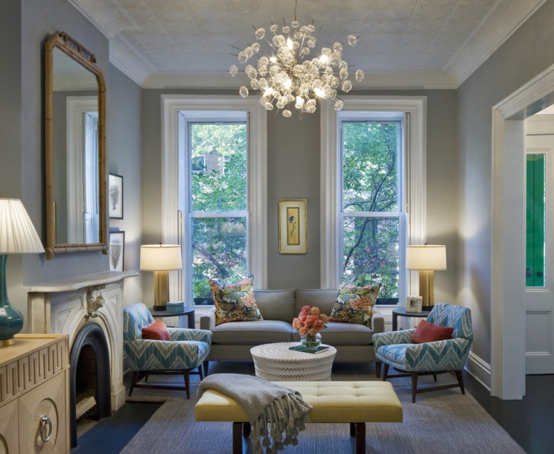 small living room in modern style small sofas with multicolored accent pillows small & round coffee table in white bubbles chandelier with brushed nickel grey walls