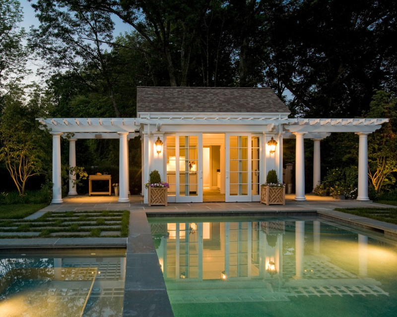 small pool house with pergola outside, sconces, glass sliding door, grey tiles, pots of plants, grass shaped like pergolla