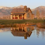 small rustic cabins body of water mountains red chairs lovely exterior