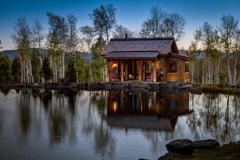 small rustic cabins body of water trees sky chairs lighting roof pillars exterior beautiful location