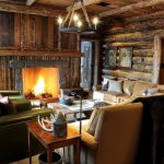 small rustic cabins family room paintings small tables couch chairs chandelier lamp fireplace logs wooden floor