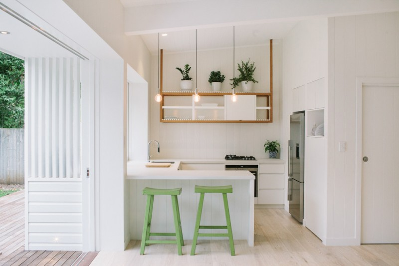 small sized contemporary kitchen idea U shaped kitchen counter and top in white green bar stools hanging wood display shelves stainless steel appliances simple hanging ball light fixtures