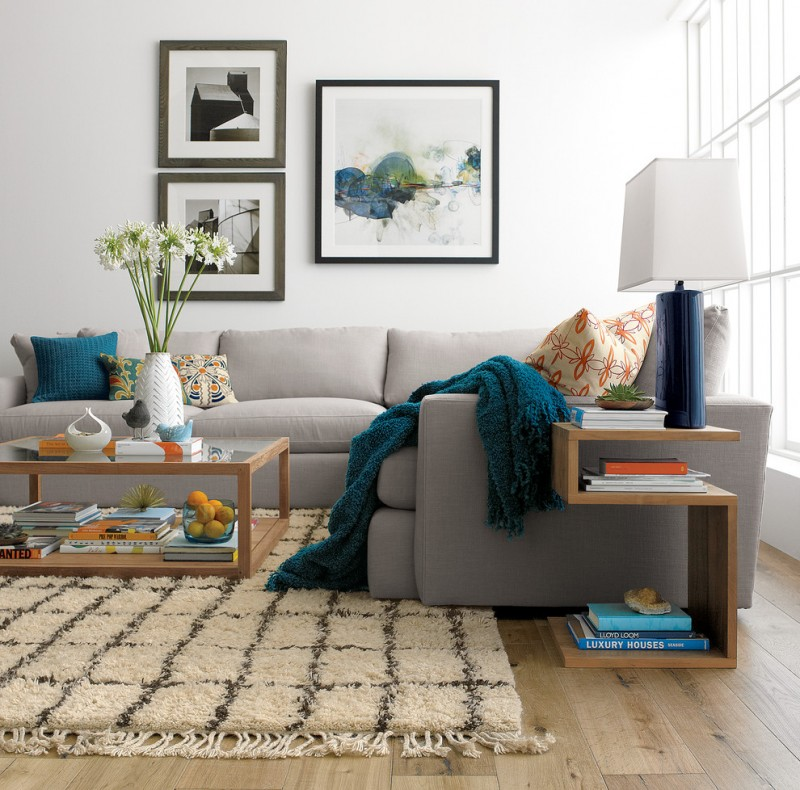soft gray couches with hand knitted blanket and accent pillows glass top center table framed by wood cozy and fluffy area rug white walls pale toned wood floors unique wood side table