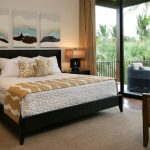 Textured Black Bed Frame With Headboard Textured White Bedding Idea Black Finished Wood Bedside Tables Rattan Chair Textured Cream Area Rug Dark Toned Wood Floors