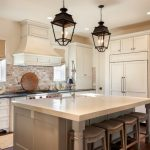 timeless u shaped eat in kitchen with a farmhouse sink, shaker cabinets, white cabinets, paneled appliances, dark hardwood floors, an island, soapstone countertops, red backsplash and brick backsplash