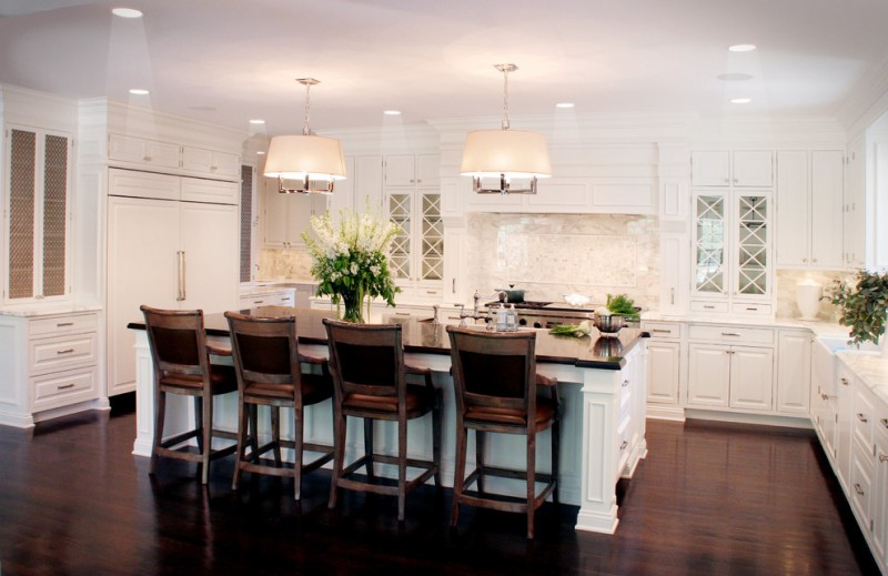 timeless u shaped kitchen with wood countertops, raised panel cabinets, white cabinets, stone slab backsplash, white backsplash and paneled appliances medium toned wooden floors