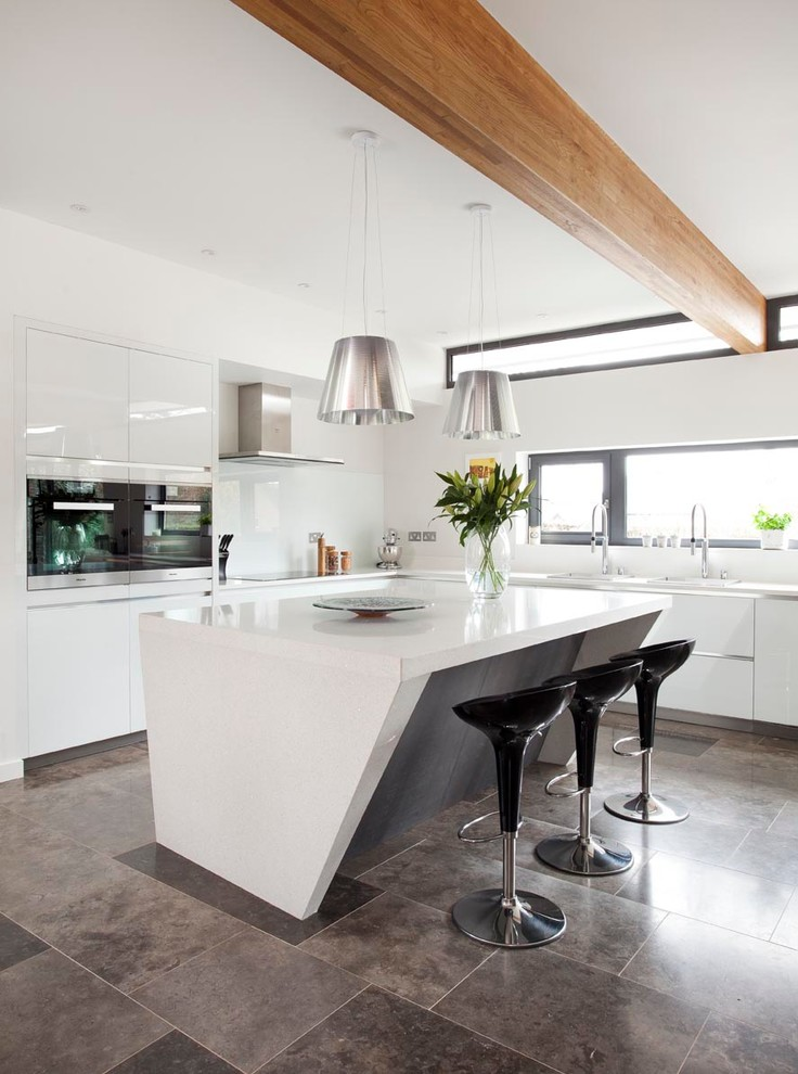 trendy contemporary kitchen glossy white cabinets expensive stainless steel appliances unique island with quartzite topin white silver toned pendant lamps black bar stools