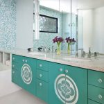 turquoise cabinet with pattern, grey granite countertops, white sink, large mirrors