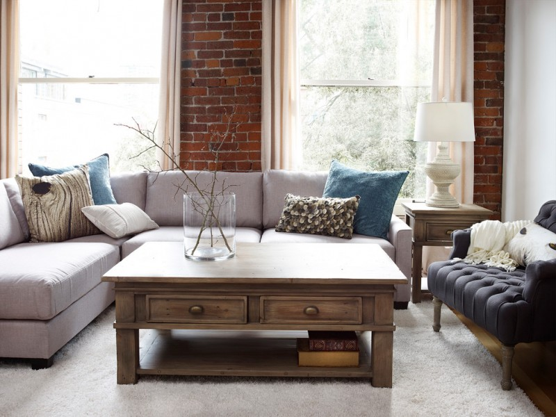 urban barn style living room furniture consisting of soft grey couches with colorful accent pillows navy blue chair hardwood center table with white top white area rug red bricks walls
