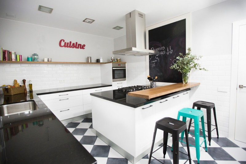 urban industrial kitchen idea with single open shelf mounted on white walls black solid countertop wooden top breakfast bar colorful bar stools black white tiles floors