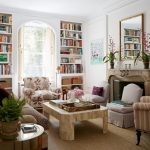 Warm And Cozy Living Room Furniture Set Arched Glass Window Surrounded By Recessed Book Racks Standard Fireplace Decorative Mirror Over Fireplace White Walls