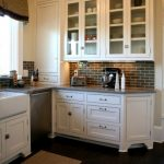 White Beaded Inset Cabinet Idea With Bottom Drawer Addition White Farmhouse Sink & Faucet White Kitchen Cabinets Dark Toned Wood Floors Red Brick Tiles Backsplash
