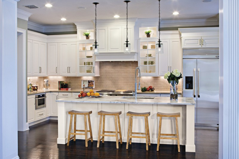 white kitchen cabinet with marble countertop wooden chairs glass pendant lights white painted floating kitchen cabinets medium toned wooden floor brick backsplash