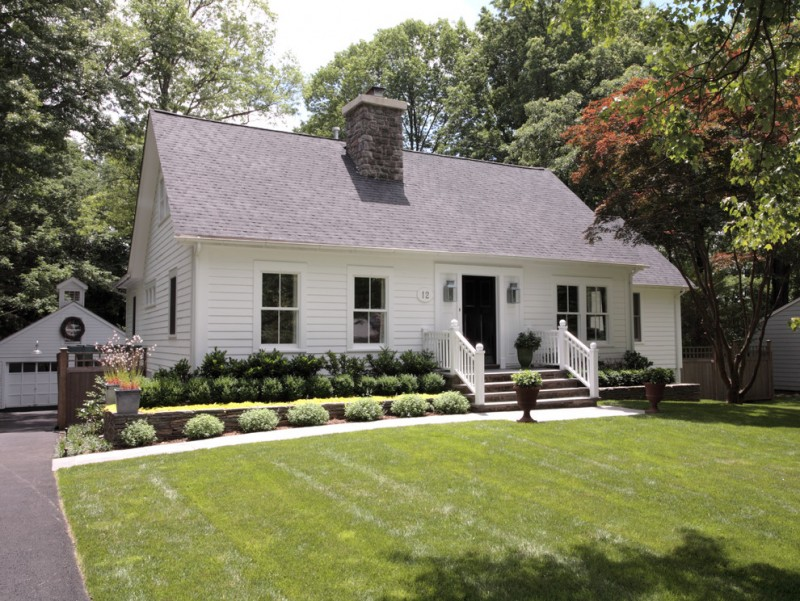 white painted deck wooden walls multicolored side gabled roof white door with glass windows evergreen shrubs flower beds stone steps white fences