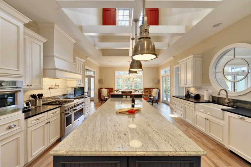 Coastal eat in kitchen with stainless steel appliances, subway tile backsplash, a farmhouse sink, granite countertops, recessed panel cabinets, white cabinets and white backsplash