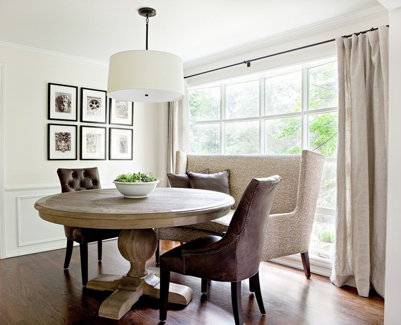 Elegant dining room with white walls and dark hardwood floors wooden round central base table small settee and chairs white pendant lamp beige curtain