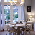 French Country Style Dining Room Baroque Style Chandelier White Round Top Dining Table French Style Dining Chairs With Grey Linen Double French Door With Glass Panels