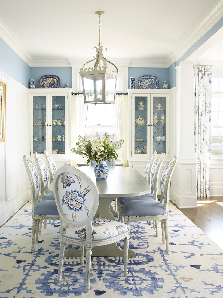 French style dining set with blue upholstery blue walls built in corner cabinets with glass doors and centered window dark hardwood floors area rug with blue colored flower motifs