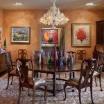 Mediterranean Style Dining Room Earthy Brown Walls Dark Finishing Corner Cabinets Dark Hardwood Dining Chairs Dark Hardwood Dining Table Crystal Chandelier Area Rug With Motifs